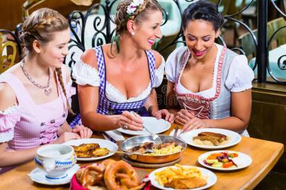 women-bavarian-pub-eating-food-dinner-schnitzel-pretzel-67600745